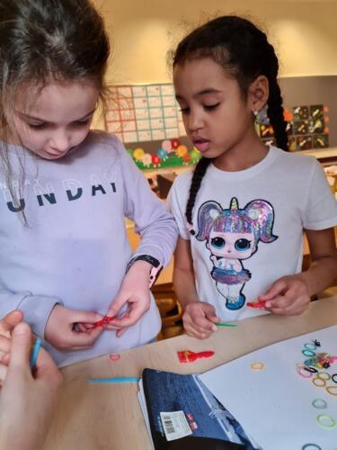 dziewczynki próbują zapleść bransoletki z gumek